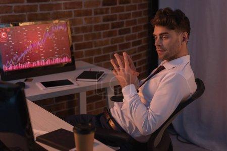 Photo pour Homme d'affaires assis près des ordinateurs avec des cartes et du café pour aller sur le premier plan flou dans la soirée - image libre de droit