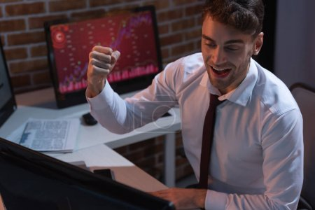 businessman showing yeah gesture near computer on blurred foreground in evening
