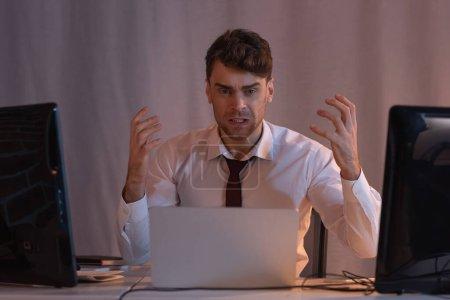 Agresywny biznesmen patrzący na kamerę w pobliżu komputerów na niewyraźnym pierwszym planie