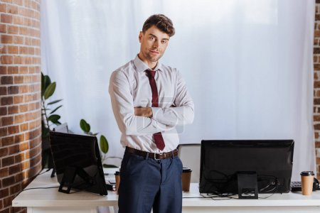 Businessman standing with crossed arms near computers in office