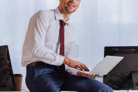 Photo pour Vue recadrée d'un homme d'affaires souriant utilisant un ordinateur portable près d'un ordinateur au bureau - image libre de droit
