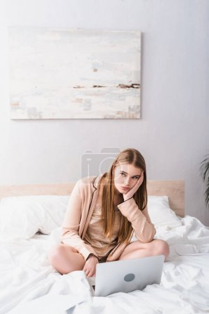 bored young woman in satin robe looking away near laptop on bed
