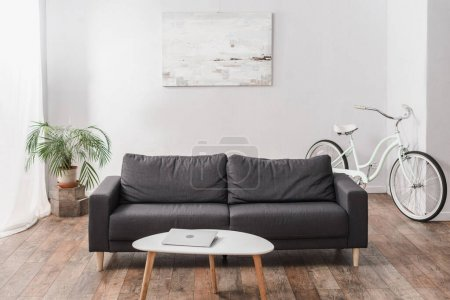 Laptop auf Couchtisch neben grauer Couch und Pflanze in moderner Wohnung