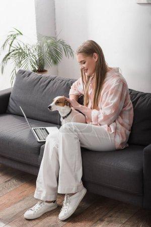 fröhliche Frau kuschelt Jack Russell Terrier neben Laptop auf Couch