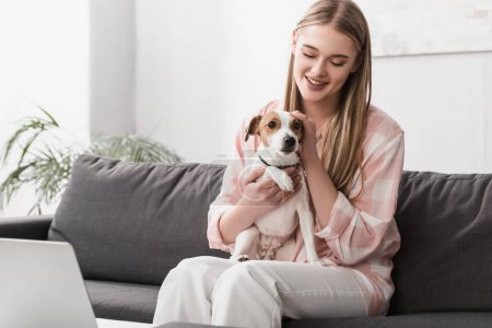 smiling woman holding in arms jack russell terrier while sitting on sofa with laptop