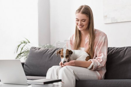 cheerful woman feeding dog with pet food in living room