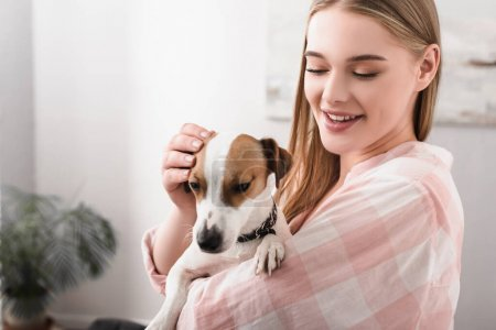 Photo pour Jeune femme gaie tenant dans les bras et câlins jack russell terrier dans le salon - image libre de droit