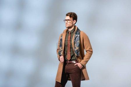 Photo pour Homme à la mode en tenue d'hiver debout avec la main dans la poche sur gris - image libre de droit