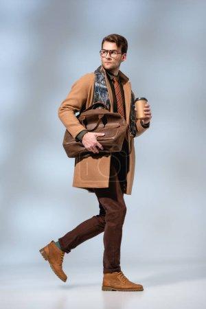Photo pour Longueur totale de l'homme élégant en manteau d'hiver tenant tasse en papier et serviette en cuir tout en marchant sur gris - image libre de droit