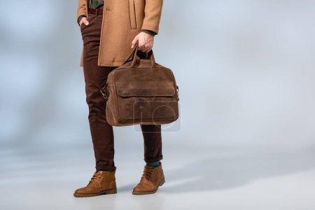 Teilansicht des stilvollen Mannes mit Lederaktentasche und mit der Hand in der Tasche auf grau