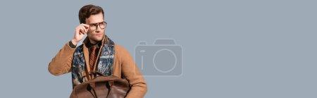 Photo pour Élégant homme en manteau d'hiver ajustant les lunettes tout en tenant la mallette en cuir isolé sur gris, bannière - image libre de droit