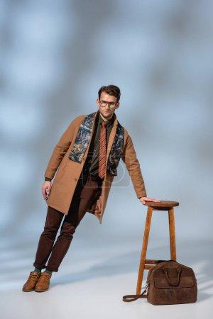 Photo pour Toute la longueur de l'homme à la mode en tenue d'hiver et des lunettes appuyées sur une chaise en bois près de mallette sur gris - image libre de droit