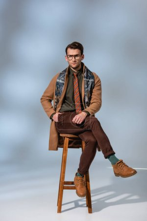 stylish man in winter outfit and glasses sitting with hand in pocket on wooden chair near briefcase on grey