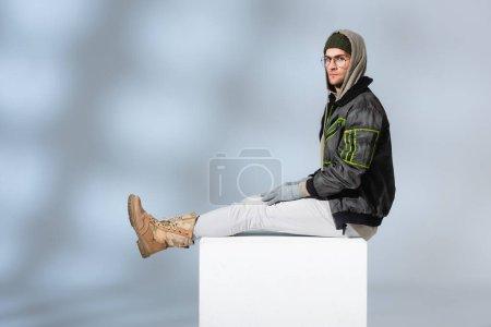 Photo pour Jeune homme en chapeau, gants et anorak assis sur cube blanc sur gris - image libre de droit