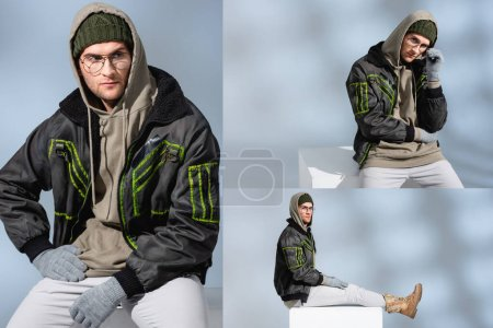 collage of trendy man in hat, gloves and parka with hand on hip sitting on white cube and adjusting glasses on grey