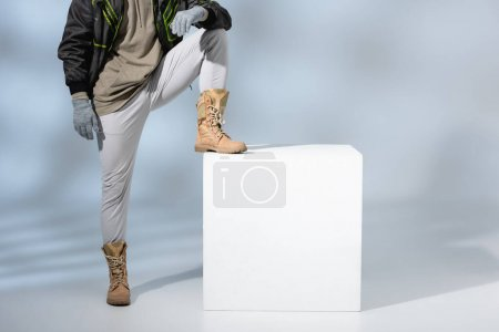 Photo for Cropped view of young trendy man in hat, gloves and anorak leaning on white cube on grey - Royalty Free Image