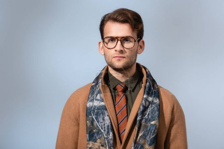 Photo for Trendy man in glasses and winter coat looking at camera on grey - Royalty Free Image