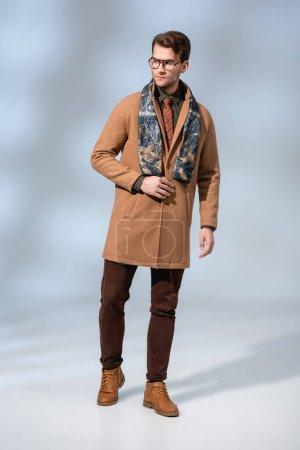 Photo pour Longueur totale de l'homme à la mode en manteau d'hiver et des lunettes debout sur gris - image libre de droit