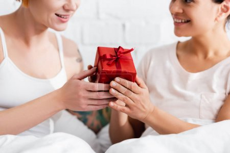 cropped view of african american woman presenting gift to lesbian girlfriend in bedroom