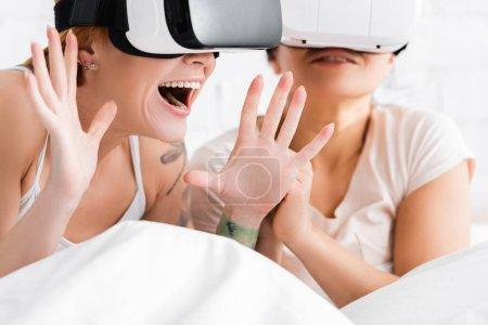 étonnante lesbienne femme gestuelle dans vr casque près afro-américaine copine au lit, fond flou