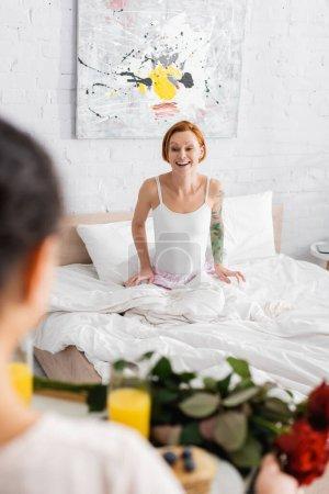 Photo pour Excité rousse femme au lit regardant lesbienne copine tenant plateau avec petit déjeuner et roses sur flou au premier plan - image libre de droit