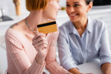 selective focus of credit card in hand of lesbian woman looking at cheerful african american girlfriend, blurred background