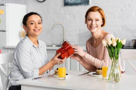 Photo pour Heureux interracial lesbienne couple regardant caméra tout en tenant des cadeaux pendant le petit déjeuner sur valentines jour - image libre de droit