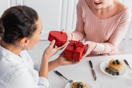 Photo pour Interracial lesbienne couple cadeau cadeaux à l 'autre pendant le petit déjeuner sur valentines jour, flou au premier plan - image libre de droit