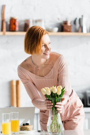 Photo for Happy redhead woman putting tulips in vase near orange juice and pancakes on table - Royalty Free Image