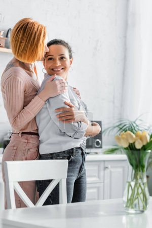 Photo pour Rousse lesbienne femme embrasser épaules de heureux afro-américain copine dans la cuisine - image libre de droit