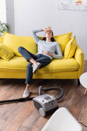 Erschöpfte Hausfrau sitzt mit geschlossenen Augen neben Staubsauger auf Sofa