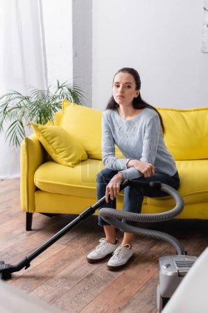 Foto de Molesto, ama de casa cansada sentado en el sofá cerca de la aspiradora - Imagen libre de derechos