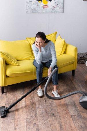 Photo pour Femme au foyer fatiguée assise sur un canapé jaune près de l'aspirateur - image libre de droit