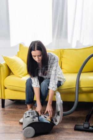 Photo pour Jeune femme au foyer changer filtre à poussière dans l'aspirateur tout en étant assis sur le canapé - image libre de droit