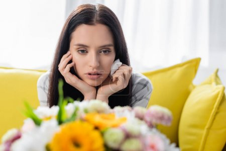 Photo for Upset allergic woman holding paper napkin near flowers on blurred foreground - Royalty Free Image
