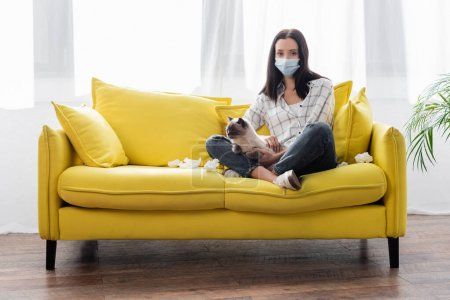allergic woman in medical mask looking at camera while sitting on sofa with cat near crumpled paper napkins