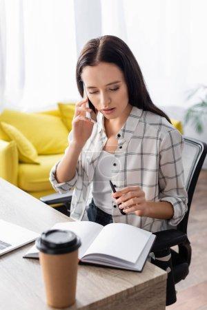 freelancer hablando en smartphone mientras sostiene la pluma cerca del cuaderno y el café para ir en primer plano borroso