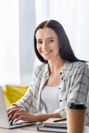 Photo for Young freelancer smiling at camera while typing on laptop near paper cup on blurred foreground - Royalty Free Image