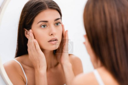 Photo for Young woman with perfect skin touching face while looking in mirror in bathroom, blurred foreground - Royalty Free Image