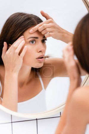 displeased young woman touching face while looking in mirror, blurred foreground