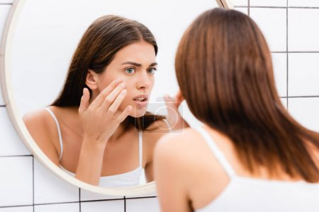 dissatisfied woman touching face while looking in mirror, blurred foreground
