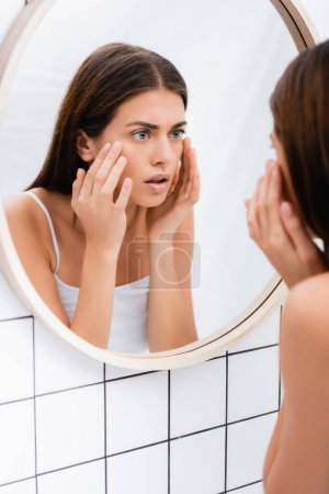 Photo for Worried young woman looking in mirror and touching face in bathroom, blurred foreground - Royalty Free Image