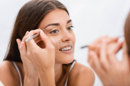 Photo for Cheerful young woman tweezing eyebrows near mirror, blurred foreground - Royalty Free Image