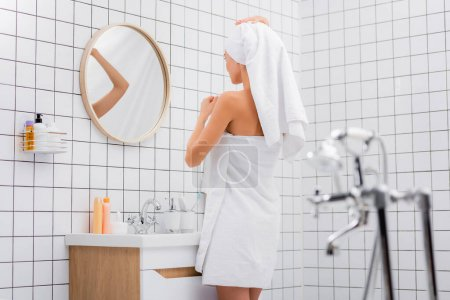 young woman, wrapped in white terry towels, standing in bathroom near mirror on blurred foreground
