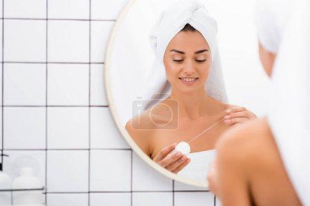 Photo pour Jeune femme avec serviette blanche sur la tête tenant fil dentaire près du miroir dans la salle de bain, avant-plan flou - image libre de droit