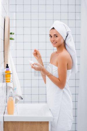 Photo pour Femme heureuse souriant à la caméra tout en tenant fil dentaire dans la salle de bain - image libre de droit