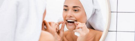 woman with towel on head flossing teeth near mirror in bathroom, blurred foreground, banner
