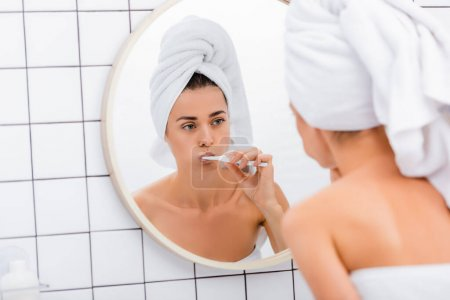 woman with white towel on head looking in mirror while brushing teeth in bathroom, blurred foreground