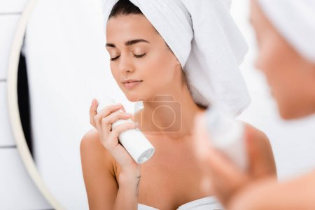 Photo for Young woman with closed eyes smelling deodorant in bathroom, blurred foreground - Royalty Free Image
