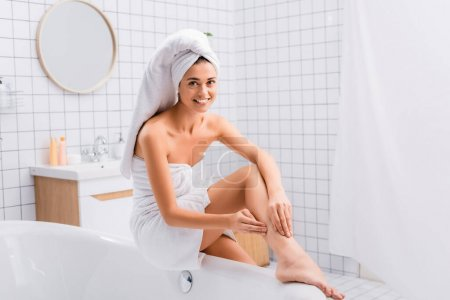 Photo for Smiling woman with white towel on head looking at camera while sitting on bathtub and applying body lotion - Royalty Free Image